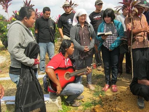 Bp. Hendra Sonito mengiringi nyanyian pemakaman dengan gitar