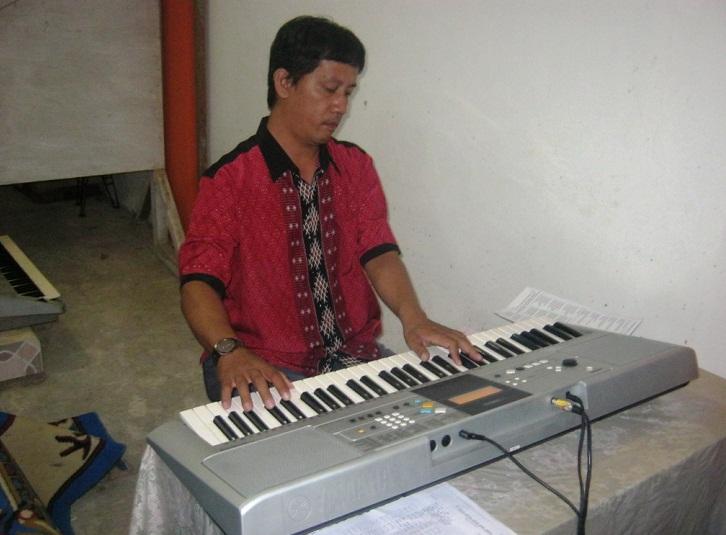 Rudy Chau memainkan musik gereja pada natal Jerora 2015